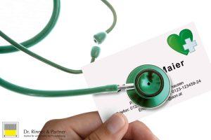 Grünes Stethoskop horcht eine Visitenkarte einer Versicherung ab