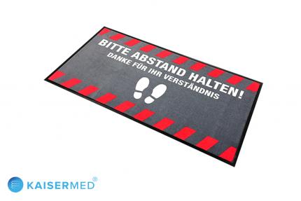 """Hinweismatte – Fußmatte bedruckt mit der Aufschrift """"Bitte Abstand halten Danke für Ihr Verständnis"""" im Querformat mit roten Signalstreifen am Rand"""