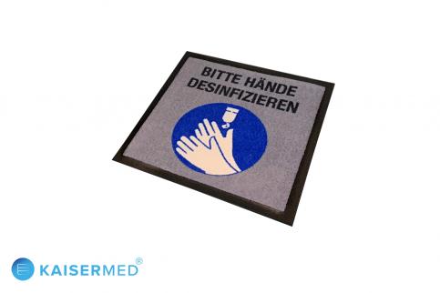 """Rechteckige bedruckte Fußmatte mit der Aufschrift """"Bitte Hände desinfizieren"""" darunter ein farbiges Bild mit Händen die desinfiziert werden"""